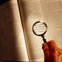 Hand holding magnifying glass over open book<br />
