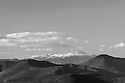Clouds above, but the summit is clear. A late season snow brightens Mt. Washington and the Presidential Range.