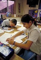 STUDENTS WRITING AT THEIR DESKS. ELEMENTARY SCHOOL STUDENTS. OAKLAND CALIFORNIA USA CARL MUNCK ELEMENTARY SCHOOL.