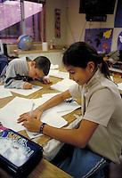 STUDENTS WRITING AT THEIR DESKS. ELEMENTARY SCHOOL STUDENTS. OAKLAND CALIFORNIA USA CARL MUNCK ELEMENTARY SCHOOL.
