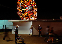 A Ferris wheel illuminates the night sky as people wearing cowboy hats stroll along the midway at the Brazoria County Fair in Texas.