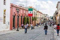 Oaxaca, Mexico, North America.  Street Scene, Mexican Flag.  Calle Alcalá.  Looking toward the Zócalo (Town Plaza) in the distance.