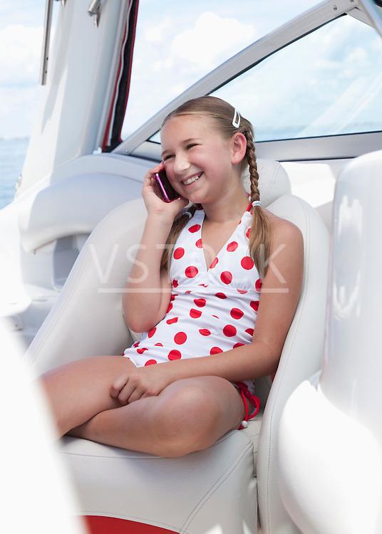 USA, Florida, St. Petersburg, Smilling girl (10-11) talking on mobile phone on yacht