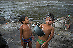"""November 07, 2014. """"Water it´s the real thing""""<br /> A child takes water from a well contaminated in Nejapa (El Salvador). The people of Nejapa in El Salvador, have no drinking water because the Coca -Cola company overexploited the aquifer in the area, the most important source of water in this Central American country. This means that the population has to walk for hours to get water from wells and rivers. The problem is that these rivers and wells are contaminated by discharges that makes Coca- Cola and other factories that are installed in the area. The problem can increase: Coca Cola company has expansion plans, something that communities and NGOs want to stop. To make a liter of Coca Cola are needed 2,4 liters of water. ©Calamar2/ Pedro ARMESTRE"""