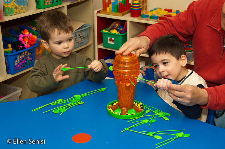 MR / Albany, New York. Clover Patch Early Childhood Day Care classroom. Clover Patch is an inclusion early childhood education program with disabled and non-disabled students at Center for Disability Services, an ungraded private school that serves individuals with disablilities. Father visits his son's classroom. His son (in front of him, boy, 5, Cuban-American / Caucasian, Cerebral Palsy, Spastic Diplegia, mainstreamed in inclusion classroom) is playing with a toy that encourages eye-hand coordination at table with a friend (boy, 4). MR: Cal8, Iso1. ID: AH-gPcp. ©Ellen B. Senisi.