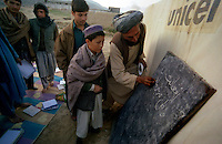 Baghlan / Afghanistan.<br /> A causa della distruzione della scuola, le lezioni si tengono all'aperto presso le tende di un campo profughi. Gli alunni sono divisi in classi maschili e femminili. Progetto realizzato con fondi UNICEF.<br /> Foto Livio Senigalliesi.<br /> Baghlan/ Afghanistan.Open air school in the northern region of Baghlan. Pupils are devided in male and female classes. Program supported by Unicef.<br /> Photo Livio Senigalliesi