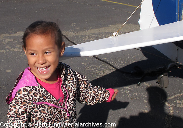 A delighted girl after climbing into an airplane cockpit during the Experimental Aircraft Association Young Eagles rally at Lampson Field (102), Lakeport, Lake County, California