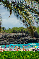 Crowds with beach umbrellas meet midday at Hapuna Beach, along the Kohala Coast of the Big Island. This white sand beach has been rated one of the best beaches in the world.