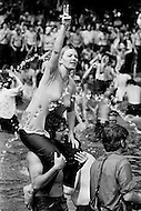 Washington, DC. May 9th,1970.<br /> A girl sits on a man's shoulders raising her hand and showing a peace sign with her fingers.<br /> More than 100,000 students stand in and around the Reflecting Pool in Washington, DC, demonstrating against the recent violence used to breakup a Vietnam War protest at Kent State University. Four Kent State students were killed, and many others injured, when members of the National Guard fired tear gas and rifles into crowds of student demonstrators protesting the Nixon administration's expansion of the Vietnam War into Cambodia.