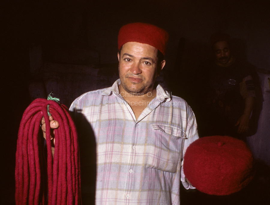"""Tunisian Hat, Chechia.  Worker Holds """"Kubitsh"""", the round felt cord forming a small tassel on top of the hat."""
