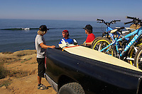 Tom, Martin and John looking at surf with surfboards and mountain bikes in back of pickup truck .Baja California , Mexico  October 2005..pic copyright Steve Behr / Stockfile
