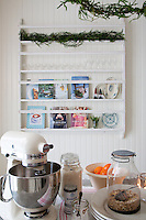 The plate rack in the kitchen contains cookery books and glasses. Preparations for Christmas baking are laid out on the kitchen island