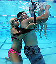"""A lifeguard with the City of Coronado, """"saves"""" Marine Sgt. Shannon Mahoe, a volunteer victim,  at the Carlsbad Community Swim Complex during the Submerged Victim Towing Relay competition."""