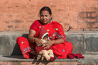 Nepal, Kathmandu, Swayambhunath.  Nepalese Mother and Daughter.  She wears a nose pin, and a bindi.  The red line between the part in her hair symbolizes that she is married.