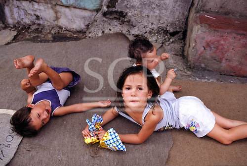 Vila Prudente, Sao Paulo, Brazil. Young children playing on a piece of carpet with bags of crisps.