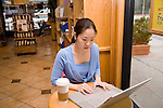 Korean female student sits at table in coffee shop by window working on laptop computer with coffee cup on table