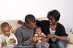2 year old toddler boy sitting near father, mother and 5 month old baby brother interested in baby toy African American horizontal
