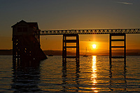 Pictured: Sunrise as seen through the RNLI boat station in Mumbles, near Swansea, Wales, UK. Sunday 13 June 2021<br /> Re: High temperatures and sunshine has been forecast for most of the UK.