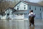 Father holding son and looking at floodwaters surrounding house