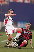 The MetroStars' John Wolyniec tackles the ball away from D.C. United's Bryan Namoff. D. C. United was defeated by the NY/NJ MetroStars 3 to 2 during the MetroStars home opener at Giant's Stadium, East Rutherford, NJ, on April 17, 2004.
