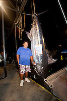 Bomboy Llanes, captain of the fishing boat Lana Kila, with a Pacific blue marlin grander at Honokohau Harbor, Kailua-Kona, Big Island.