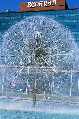 """Belgrade, Serbia, Yugoslavia. Water fountain in form of a globe in front of the Continental Belgrade Hotel with """"Beograd"""" sign on the top."""