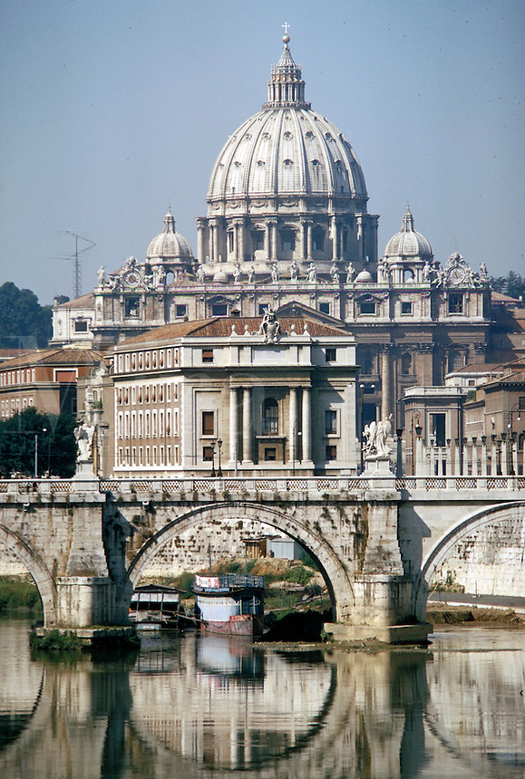 The dome of St Peter's Cathedral in the Vatican, is visible beyond an ornate stone bridge. Rome, Italy.