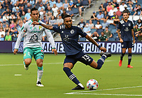 KANSAS CITY, KS - AUGUST 10: Amadou Dia #13 of Sporting Kansas City clears a ball upfield as Jose Rodriguez #8 of Club Leon FC tries to catch up to him during a game between Club Leon FC and Sporting KC at Children's Mercy Park on August 10, 2021 in Kansas City, Kansas.