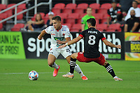 WASHINGTON, DC - JULY 7: Brandon Aguilera #28 of Liga Deportiva Alajuense battles for the ball with Felipe Martins #18 of D.C. United during a game between Liga Deportiva Alajuense  and D.C. United at Audi Field on July 7, 2021 in Washington, DC.