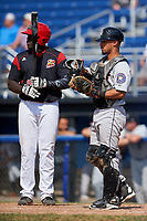 Tri-City ValleyCats catcher Carlos Canelon (1) puts his mask on as Lazaro Alonso (19) gets ready to bat during a game against the Batavia Muckdogs on July 16, 2017 at Dwyer Stadium in Batavia, New York.  Tri-City defeated Batavia 13-8.  (Mike Janes/Four Seam Images)