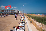 Cyclists and beachgoers sit on benches and watch the passersby on the boardwalk at Rehoboth Beach, Delaware, USA.