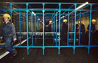 Switzerland. Canton Lucerne. A group of men with yellow helmets build bunk beds in the Sonnenberg tunnel in Lucerne during the largest civil defense exercise ever held in the country. From 16 to 21 November 1987, almost 1200 men and women converted a motorway tunnel into perhaps the world's largest bunker structure. The civil protectors had to prove during the exercise «Ameise » ( Ants in english) that in an emergency more than 20,000 inhabitants of the city of Lucerne could survive here in the mountain for two weeks. The Sonnenberg Tunnel is a 1,550 m  long motorway tunnel, constructed between 1971 and 1976. At its completion it was also the world's largest civilian nuclear fallout shelter, designed to protect 20,000 civilians in the eventuality of war or disaster. Based on a federal law from 1963, Switzerland aims to provide nuclear fallout shelters for the entire population of the country. The construction of a new tunnel near an urban centre was seen as an opportunity to provide shelter space for a large number of people at the same time. The giant bunker was built between 1970 and 1976 at a cost of 40 million Swiss francs. The shelter consisted of the two motorway tunnels (one per direction of travel), each capable of holding 10,000 people in 64 person subdivisions. A seven story cavern between the tunnels contained shelter infrastructure including a command post, an emergency hospital, a radio studio, a telephone centre, prison cells and ventilation machines. The shelter was designed to withstand the blast from a 1 megaton nuclear explosion 1 kilometer away. The blast doors at the tunnel portals are 1.5 meters thick and weigh 350 tons. The logistical problems of maintaining a population of 20,000 in close confines were not thoroughly explored, and testing the installation was difficult because it required closing the motorway and rerouting the usual traffic. The only large-scale test, a five-day exercise in 1987 to practice converting the road tunnels into