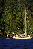 Woman aboard saling yacht 'Heron', at anchor off jungle shore of The Grottoes, Tahiti, French Polynesia