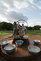 BURKINA FASO, Gaoua , women fetch drinking water from water pump with turning wheel in village / Burkina Faso, Gaoua, Frauen holen Wasser von einem Brunnen mit Drehpumpe