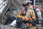 A firefighter using a hoseline to extinguish a hot spot at a fire scene