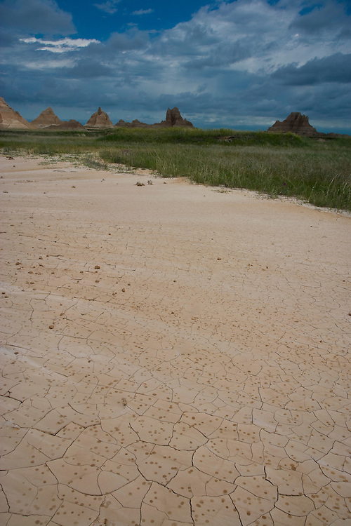 Rain drops on mud plates and approaching storm clouds over the badland formations near the Door/Window Trail; Badlands National Park, SD