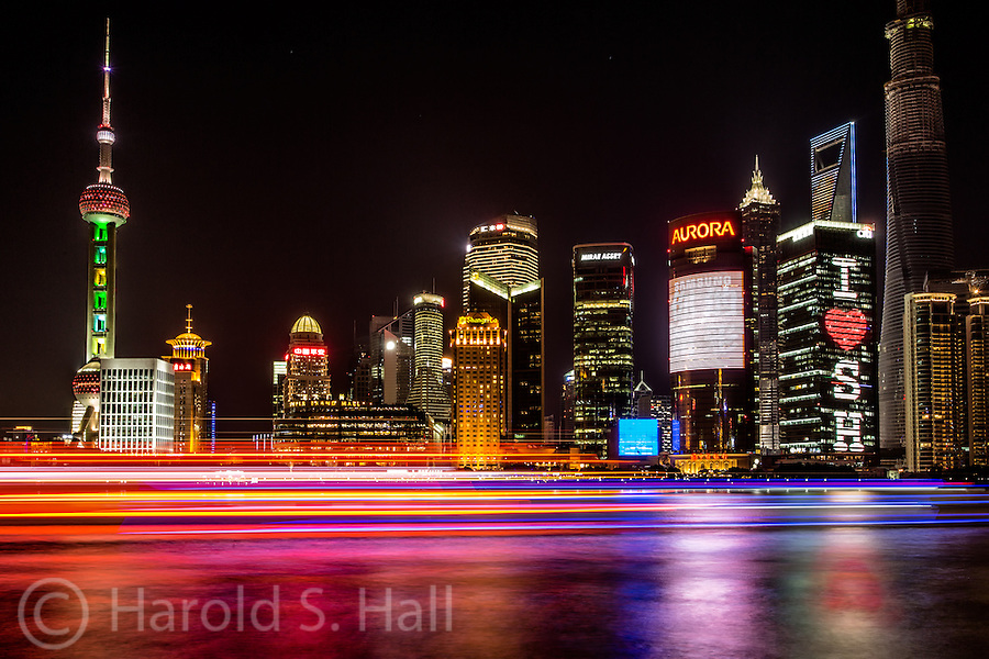 The Shanghai Bund has dozens of historical buildings, lining the Huangpu River, that once housed numerous banks and trading houses from across Europe.  Across the river, modern buildings reach ever higher where, unlike the Bund, building heights are unrestricted.  The tall building on the left is a radio tower.  Notice the taller dark building on the right still under construction.
