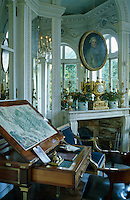 A map is displayed on a Louis XVI architect's table in the mirrored Octagonal Salon