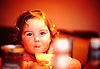 2 year old girl,sitting at table,eating,chubby cheeks,bright eyes.<br />