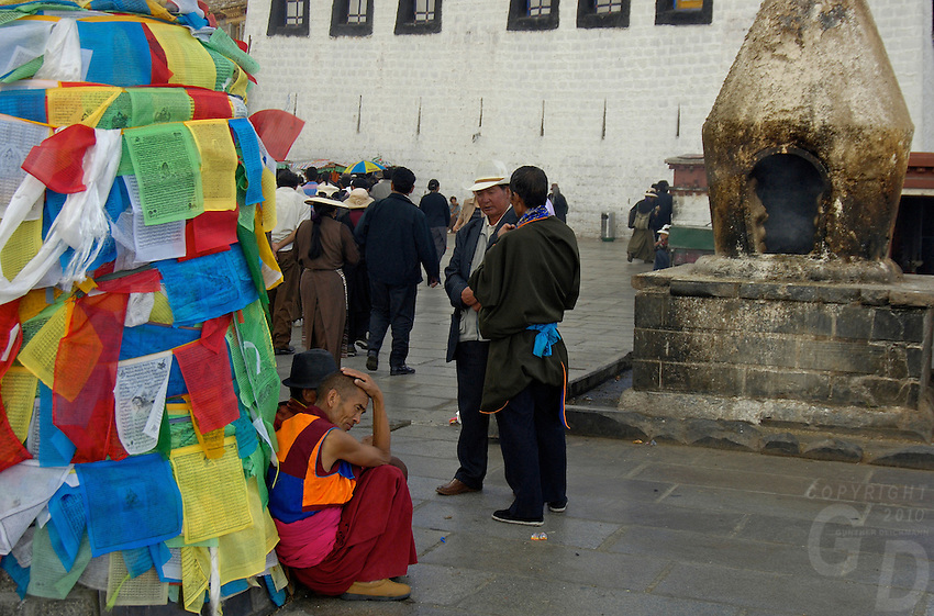 Tibetan gather near Jokhang Temple, Lhasa.Giant Incense Burner in the background at the Jokhang Temple,.The Jokhang Temple is one of Tibet's holiest shrines, originally built in 647 A.D. in celebration of the marriage of the Tang Princess Wencheng and the Tubo King Songtsen Gampo. In front of the gate is a stone Tablet of Unity from the Tang Dynasty; inscribed are both Chinese characters and Tibetan script. Nearby is the stump of the willow tree said to have been planted by Princess Wencheng herself; two younger willow trees now flank the stump of the first tree...Located in the center of old Lhasa, the temple was built by craftsmen from Tibet, China, and Nepal and thus features different architectural styles. The temple is also the spiritual center of Tibet and the holiest destination for all Tibetan Buddhist pilgrims. In the central hall is the Jokhang's oldest and most precious object--a gold statue of a seated 12-year-old Sakyamuni. This is said to have been transported to Tibet by Princess Wencheng from her home in Changan in 700 A.D. Other precious antiques in the temple include a silk portrait of Buddha from the Tang Dynasty and a pearl gown and gold lamp from the Ming Dynasty. The three-leafed roof of the Jokhang offers splendid views of the bustling Barkhor market and across to the Potala Palace..