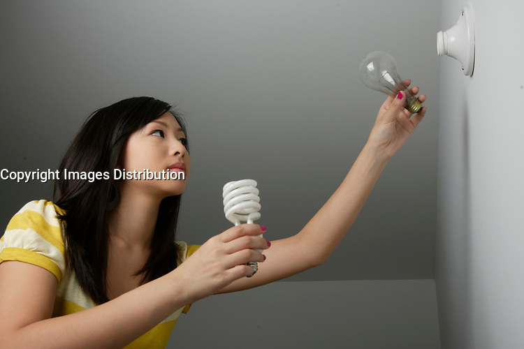 Montreal (Qc) CANADA, July 24, 2007 - Model Released photo- A young asian woman replace an incandescent light bulb by an efficient compact fluorescent light bulb.(CFL)<br /> <br /> A compact fluorescent lamp (CFL), also known as a compact fluorescent light bulb is a type of fluorescent lamp designed to replace an incandescent lamp. Many CFLs can fit in the existing incandescent light fixtures.<br /> <br /> Compared to incandescent lamps of the same luminous flux, CFLs use less energy and have a longer rated life. In the United States, a CFL can save over US$30 in electricity costs over the lamp's lifetime compared to an incandescent lamp and save 2000 times their own weight in greenhouse gases[<br /> <br /> photo : (c) images Distribution