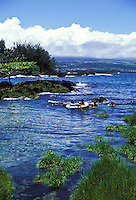 Children in a rubber raft float in the ocean near Hilo Bay, Hawaii