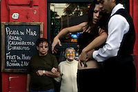 People watch Ceci tango dance with her dancing partner Meme outside a restaurant in the El Caminito area of Buenos Aires where Ceci and Meme work. They dance together most of the time as it is better to have partners who know each other's movements and can choreograph together.