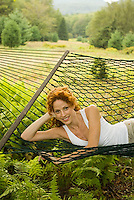 Red haired woman laying in hammock<br />