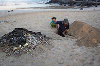 Jimbaran, Bali, Indonesia.  Man Digging a Pit on the Beach to Bury Trash.