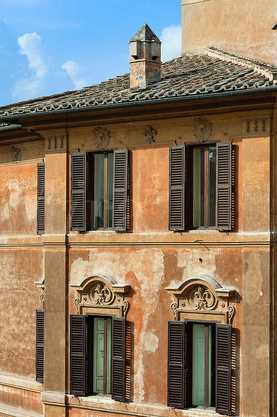 Exterior building detail with shuttered windows and terra cota roof, Rome, Italy