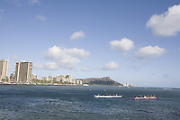 Outrigger canoes being paddled off the shore of Waikiki, with Diamond Head in the background