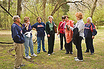 Mature females stand together in Rowan Woods listening to one senior man lecturing about the .William Faulkner home and woods in Oxford, Mississippi.