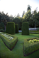 Topiary obelisks in the formal garden echo the angular box hedges that contain delicate flowerbeds