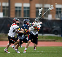 Grant Catalino (1) and Bryn Holmes (17) of Maryland try to squeeze Joe Kelly (17) of Penn at Ludwig Field in College Park, Maryland.